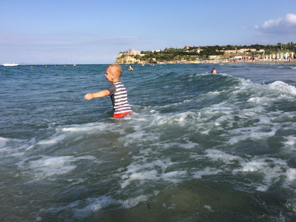 Преодолевая накатывающие волны, Тёмка идёт в море