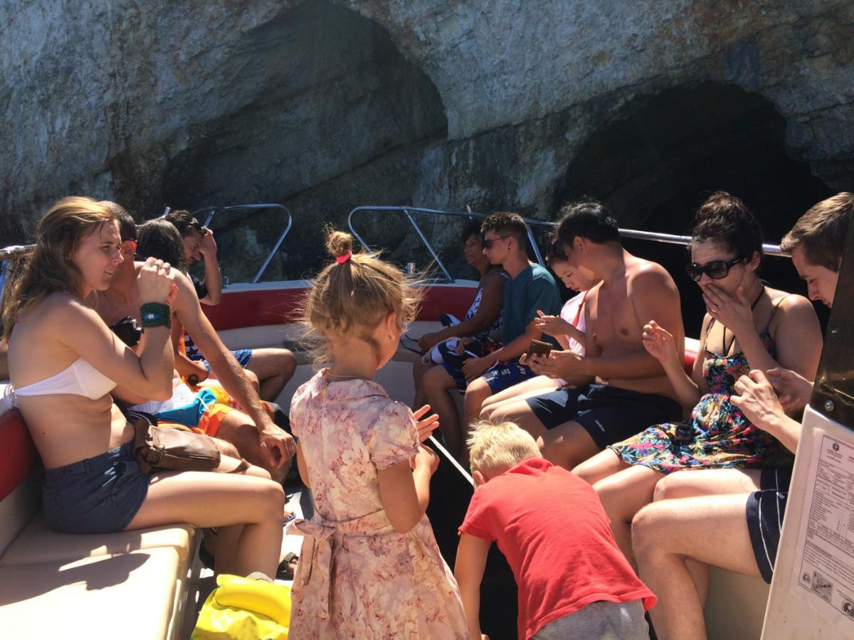 Туристы на лодке во время экскурсии по Blue Caves