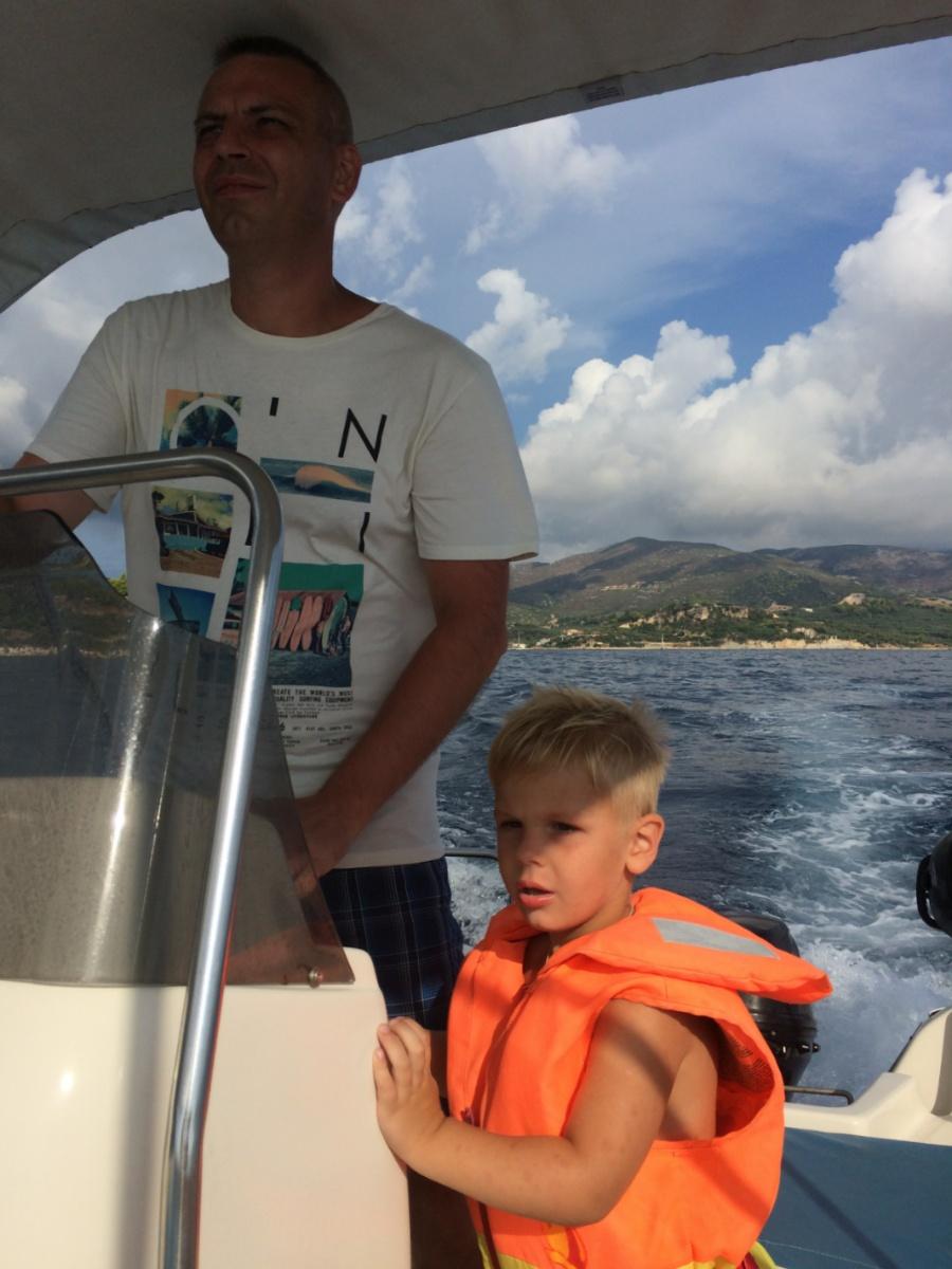 Тёма с папой стоят за штурвалом лодки