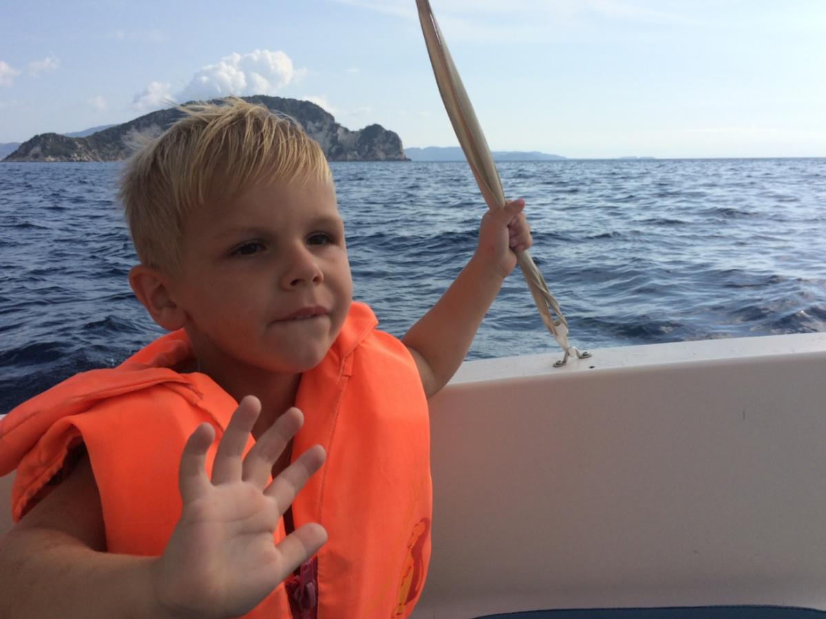 Тёма на лодке на фоне острова Марафонити