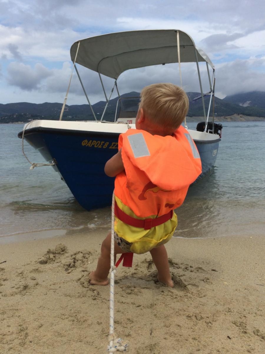 Тёма вытаскивает лодку на берег черепашьего пляжа