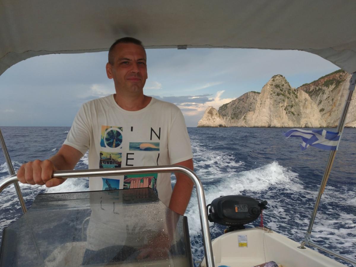 Папа за штурвалом лодки плывёт к острову Марафонити