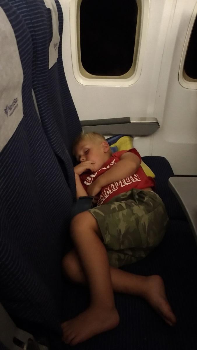 Тёмка спит на борту самолёта